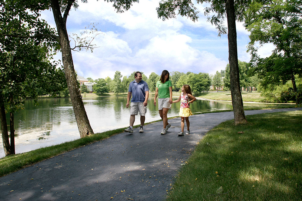 People walking on a trail around a lake in New Albany Ohio